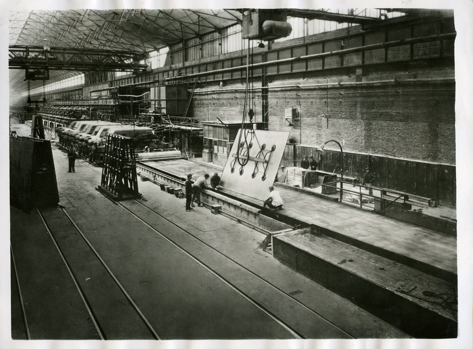 Manipulation d'une feuille de verre pour l'entreposage à la fin de la ligne de float, Glaceries de Moustiers-sur-Sambre, vers 1960